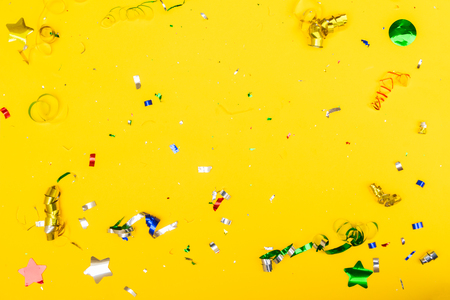 Bright colorful carnival or party scene of metalic colorful confetti on yellow background. Flat lay style, birthday or party greeting card background