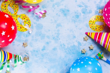 Bright colorful carnival or party border of balloons, streamers and confetti on blue table background. Flat lay style, birthday or festive party greeting card with copy space.