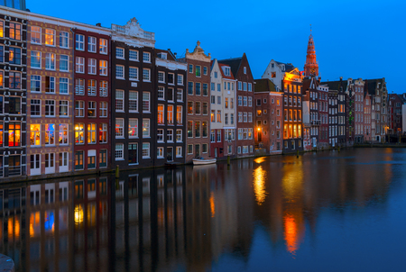 Houses over canal with mirror reflections in water at blue night, Amsterdam, Netherlands