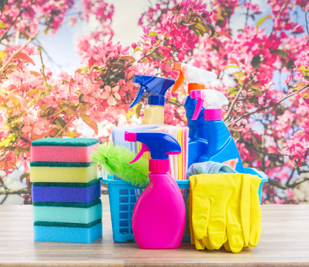 Spring cleaning concept - colorful sprays bottles and rubbers on wooden table over spring background Stock Photo