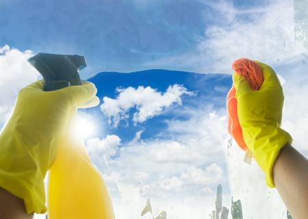 Spring cleaning - someones hands in yellow gloves with spray and ruber cleaning window, spring bright blue sky in background Standard-Bild