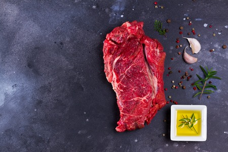 Raw beef steak meat with spices on dark background, top view flat lay scene