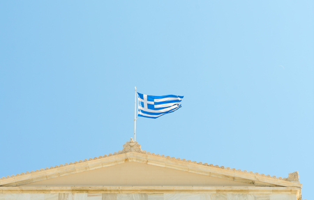 Flag of Greece on Athenian classical building in clear blue sky