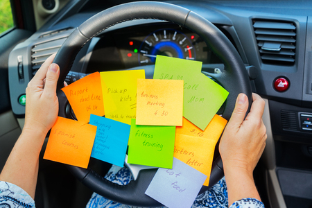 Two hands holding driving wheel and to do list in a car - busy day concept Stockfoto