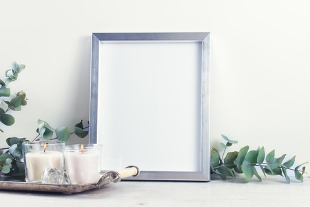 White room interior decor with burning hand-made candle and poster mock up