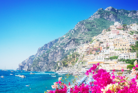 Thyrenian Sea and row of umbrellas on beach of Positano with flowers - famous old italian resort, Italy, toned image