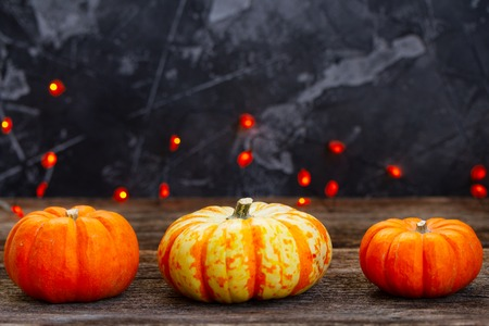 Three raw pumpkins on wooden table