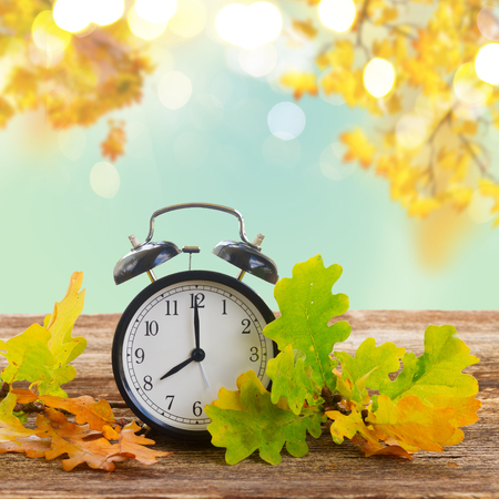 Autumn time - fall leaves with alarm clock border ob fall garden background Stock Photo