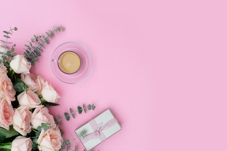 Morning cup of coffee with gift or present box and rose flowers on pink table from above, flat lay scene with copy space