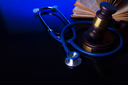 Wooden law gavel with stethoscope on blue with copy space - medical law and justice concept