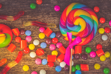 Colorful varies candies on wood close up background, retro toned