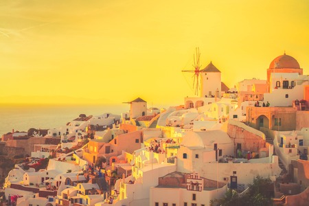 famouse soft orange sunset of Oia with windmill, Santorini island, toned Stock Photo