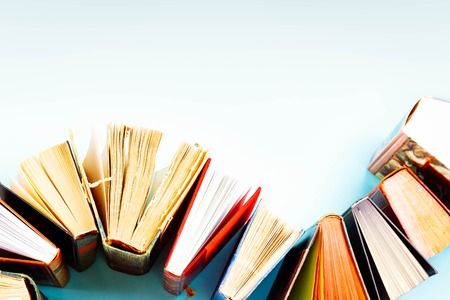 Pile of old books on blue background with copy space, retro toned