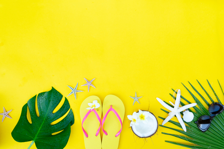 Summer flat lay border with green leaves, cocnut and flip-flops with copy space