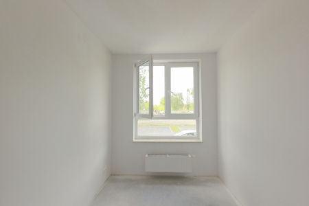 Empty unfinished room with window in a new constructed building