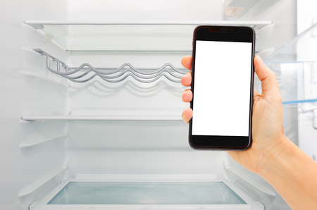 empty white open fridge with hand holding modern phone with copy space