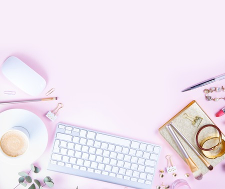 Flat lay home office workspace - white modern keyboard with female accessories and coffee, copy space on pink background