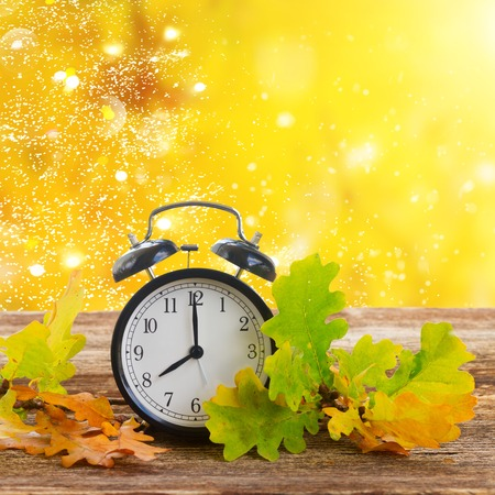 Autumn time - fall leaves with alarm clock close up over fall foliage background Stock Photo