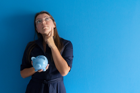 Woman holding blue piggy bank with coins, savings concept