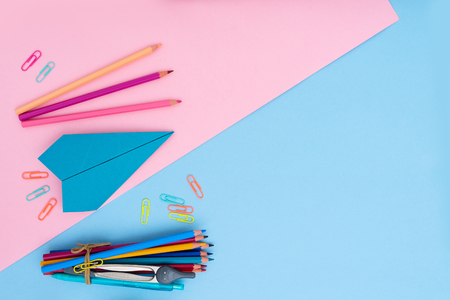 Back to school styled flat lay scene with school supplies on pink and blue background Stock Photo