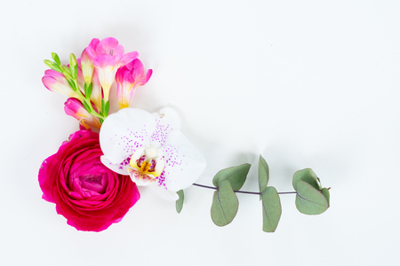 Flowers composition made of orchid and ranunculus ranunculus flowers on white background. Flat lay scene with copy space