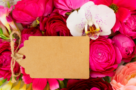 Flowers composition. Floral background made of flowers. Flat lay, top view, copy space on paper tag