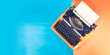 Workspace with orange vintage retro typewriter on blue and orange background, toned