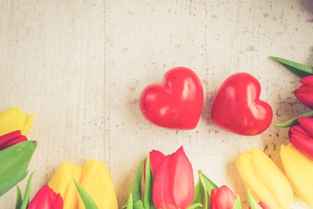 yellow and red tulips with with two loving hearts for valentines day, top view close up, toned Stock Photo