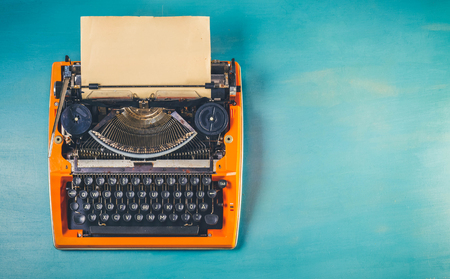 Workspace with orange vintage typewriter on blue wooden table background, toned