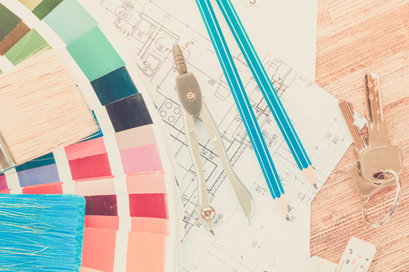 Interior designers working desktop with architectural plan of the house, keys, color palette and brushes retro toned Archivio Fotografico