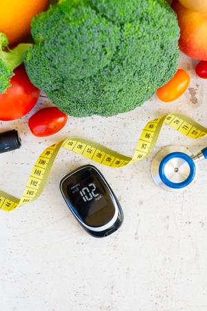 Verduras crudas con medidor de glucosa en sangre, concepto de dieta saludable para la diabetes Foto de archivo