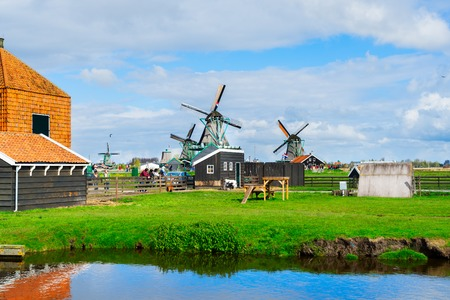 traditional Dutch rural spring scene with canal and windmills of Zaanse Schans, Netherlands