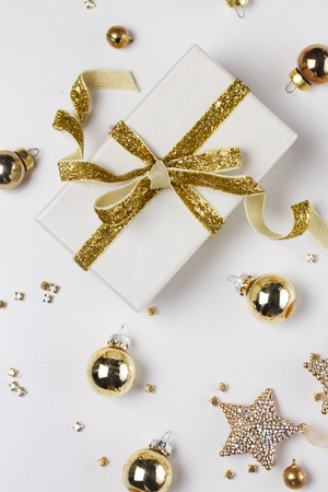 Christmas flat lay styled scene with git box with golden bow knot on white background Stock Photo