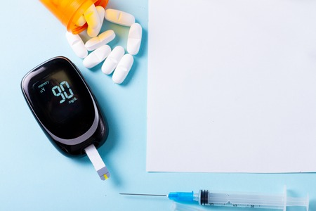 White pills in orange bottle with blood glucose meter on blue background, copy space on white paper note