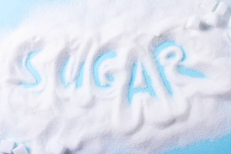 Sugar word in sugar on blue background Imagens