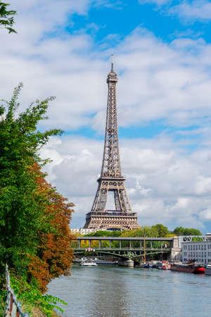 famous Eiffel Tour over Seine river with green trees, Paris, France