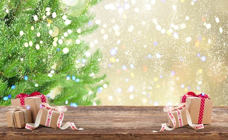 Carton gift boxes on wooden table, border with christmas tree in background Stock Photo