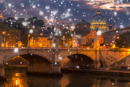 St. Peters cathedral dome over bridge and river in Rome at winter night with snow, Italy