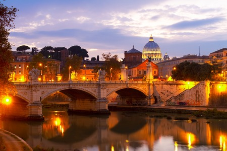 St. Peters cathedral dome over bridge and river in Rome illuminated at night, Italy