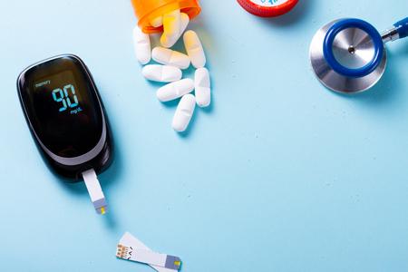 Pillole bianche in bottiglia arancione con misuratore di glucosio nel sangue su blu con spazio di copia