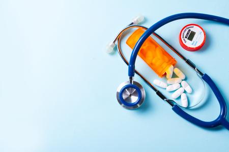 Weiße Pillen in orangefarbener Flasche mit Stethoskop auf Blau mit Kopierraum