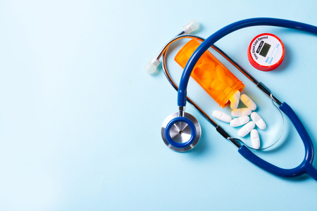 White pills in orange bottle with stethoscope on blue  with copy space Stockfoto