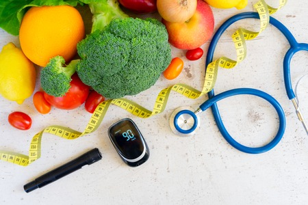 Raw vegetables with blood glucose meter, lancet and stethoscope, , diabetes healthy diet concept