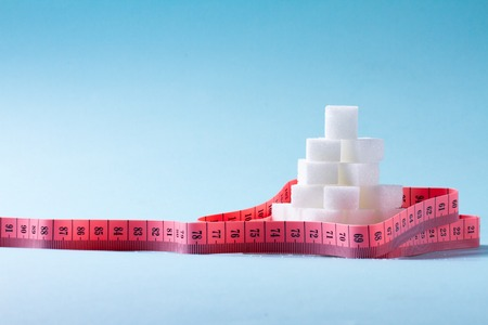 Pile of sugar cubes with measuring tape on blue with copy space