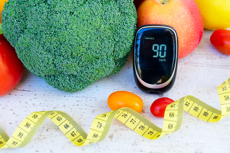 Raw vegetables with blood glucose meter with measuring tape, diabetes healthy diet concept Stock Photo