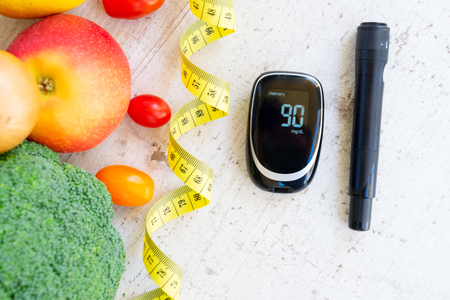 Raw vegetables with blood glucose meter and lancet, diabetes healthy diet concept Stock Photo