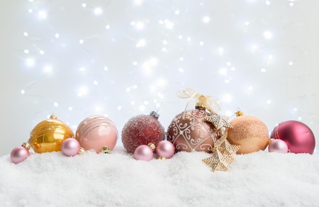 White christmas with snow - pink and golden balls with festive light Фото со стока