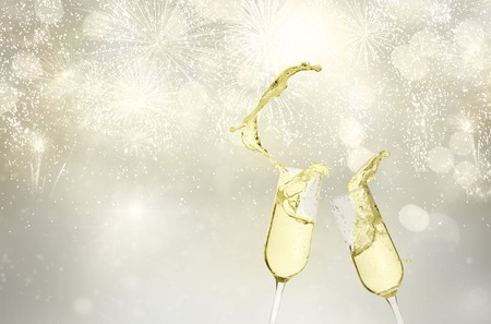 Two festive champagne glasses with splashes on silver bokeh  with lights, Christmas toast