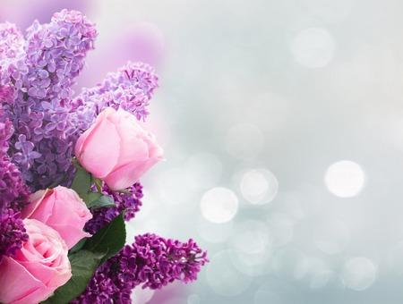 Strauß frischer lila lila Blumen mit rosa Rosen über Grau mit Kopierraum