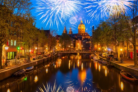 Church of St Nicholas and red lights quater over old town canal at night with fireworks, Amsterdam, Holland Stock Photo